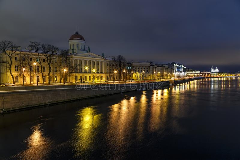 Neva river embankment with historical buildings on the shore and reflection of night lights in the water, beautiful sunset sky. Neva river embankment with stock photos