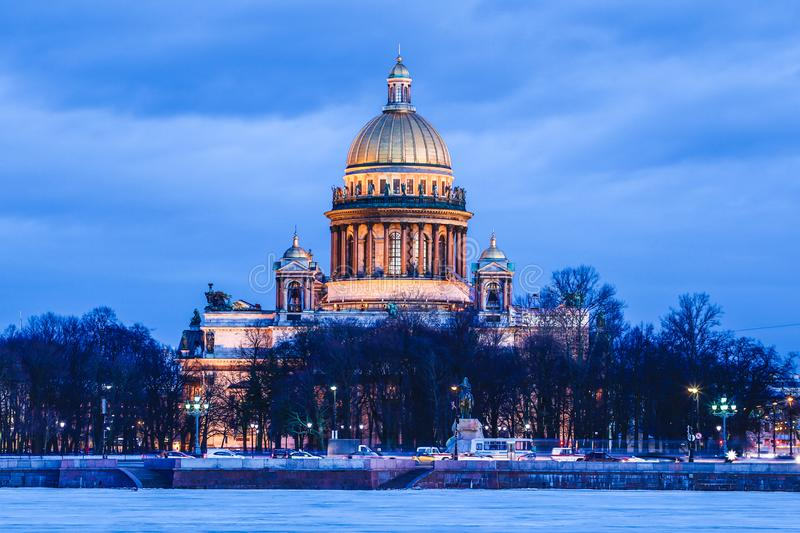 Neva river under the ice and snow and Beautiful Saint Isaac`s Cathedral or Isaakievskiy Sobor in Saint Petersburg, Russia. In the cold winter evening or night royalty free stock image