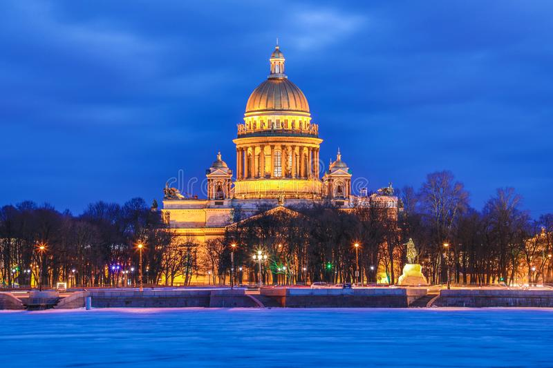 Neva river under the ice and snow and Beautiful Saint Isaac`s Cathedral or Isaakievskiy Sobor in Saint Petersburg, Russia. In the cold winter evening or night stock image