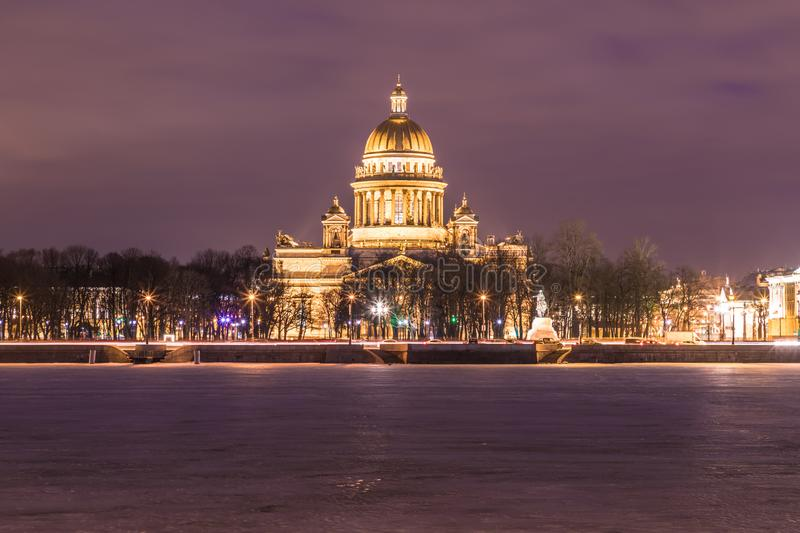 Neva river under the ice and snow and Beautiful Saint Isaac`s Cathedral or Isaakievskiy Sobor in Saint Petersburg, Russia. In the cold winter evening or night stock images