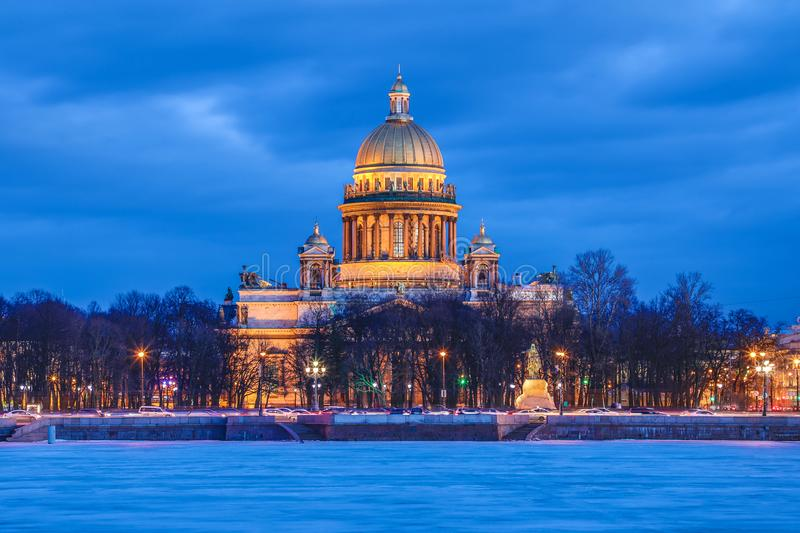 Neva river under the ice and snow and Beautiful Saint Isaac`s Cathedral or Isaakievskiy Sobor in Saint Petersburg, Russia. In the cold winter evening or night royalty free stock images