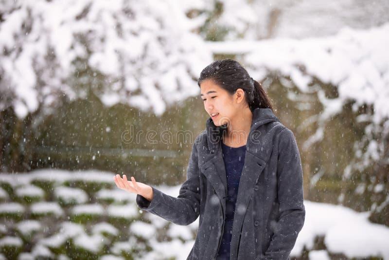 Nevadas de goce extendidas de la muchacha de los brazos adolescentes del aire libre en invierno foto de archivo