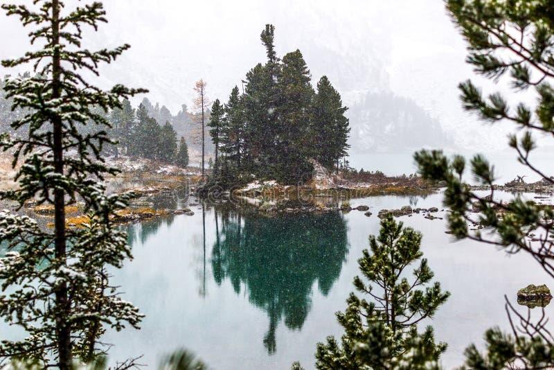 Nevadas en el lago de la montaña La reflexión de rocas y los árboles en el agua emergen fotos de archivo