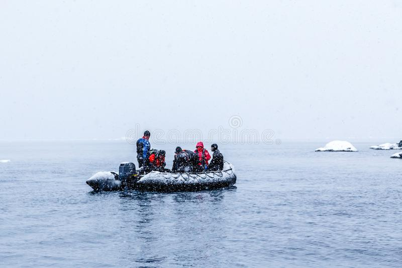 Nevadas sobre el barco del zodiaco con los buceadores polares congelados cerca de Almirante Brown, península antártica imagen de archivo