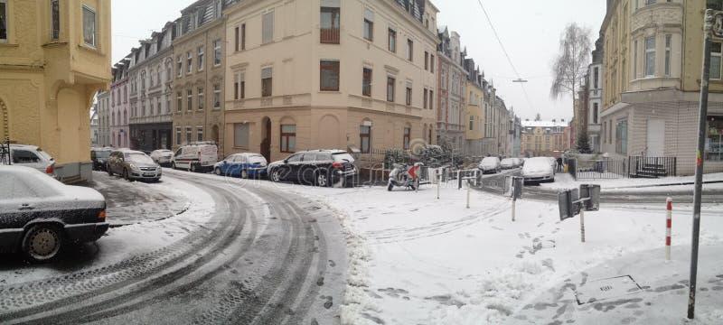 Nevado en esquina de calle montañosa en Wuppertal, Alemania con los coches parqueados fotografía de archivo libre de regalías