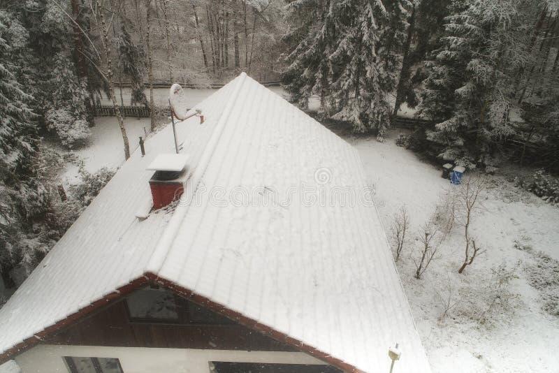 Nevado, tejado, de una casa separada en un bosque con una antena de satélite nevada y los pinos en el borde fotos de archivo