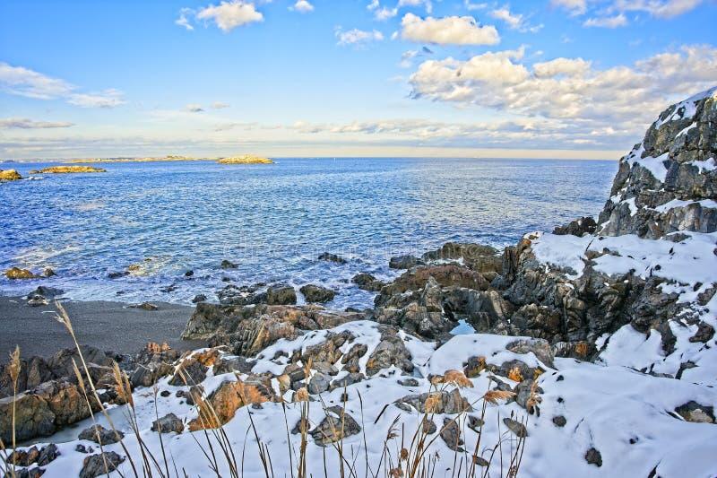 Nevado y rocosos pasan por alto del océano y de la costa durante invierno imágenes de archivo libres de regalías