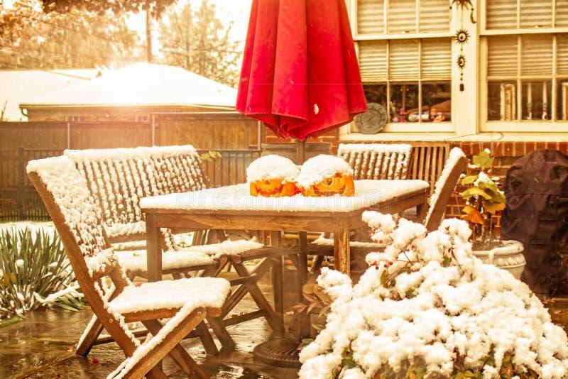 Neve in anticipo - tavola e sedie all'aperto con due lanterne della presa o e un ombrello di sole su un patio durante la doccia d fotografia stock libera da diritti