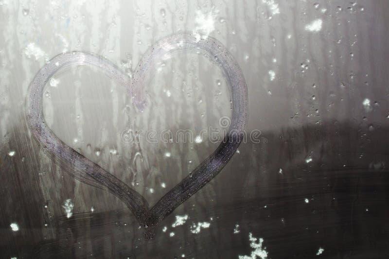 Neve appiccicosa su un cuore disegnato a mano sul vetro sudato immagini stock libere da diritti