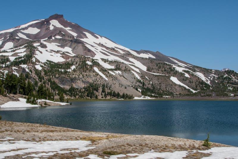A neve atrasa-se em torno dos lagos verdes fotografia de stock royalty free