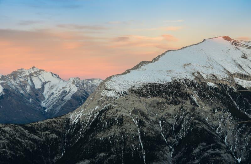 A neve bonita tampou montanhas contra o céu crepuscular em Banf imagens de stock