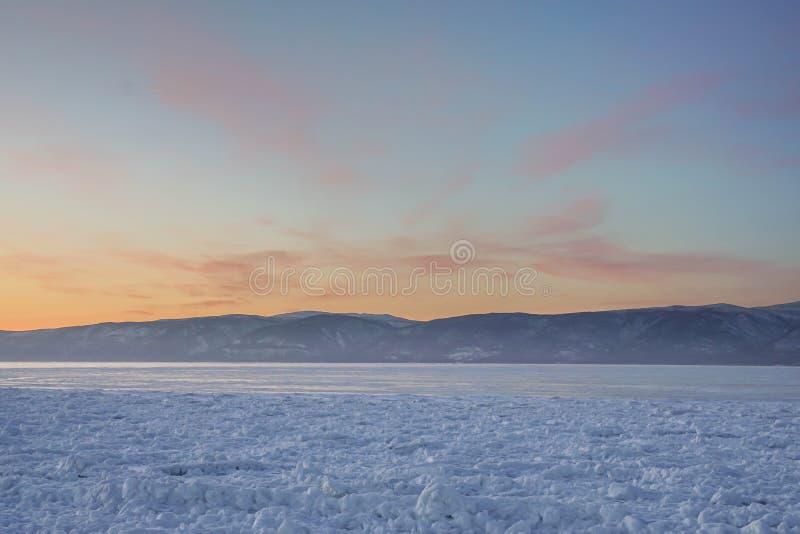 Neve branca no lago congelado no céu do por do sol em Baikal fotos de stock royalty free