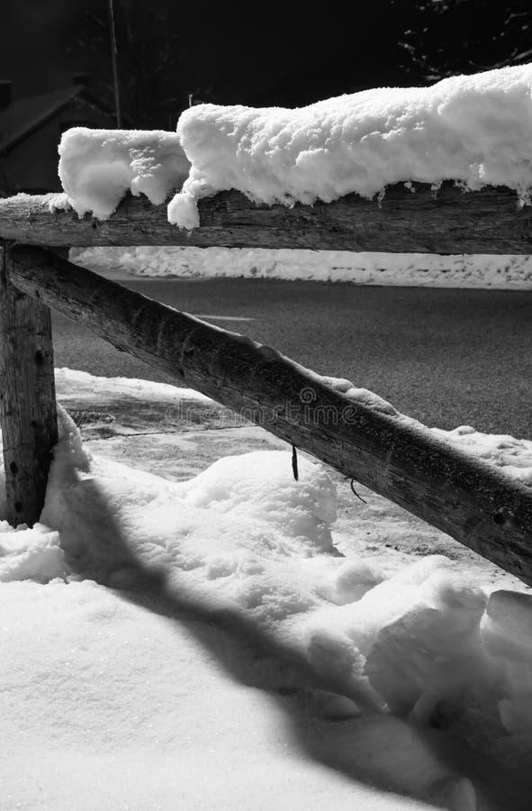 Neve caduta orario invernale sul motivo di legno del recinto alla notte fotografia stock