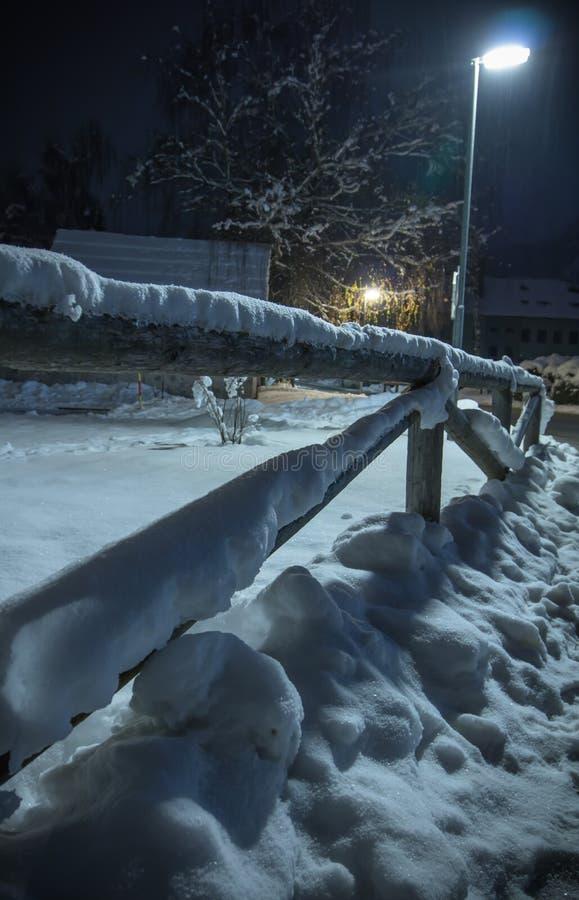Neve caduta orario invernale sul motivo di legno del recinto alla notte fotografie stock