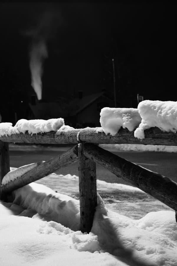Neve caduta orario invernale sul motivo di legno del recinto alla notte con fumo che esce il camino con luce posteriore fotografie stock libere da diritti