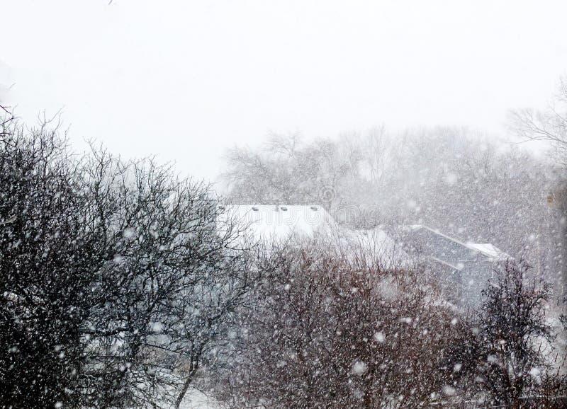 Neve caindo em árvores e casa imagens de stock