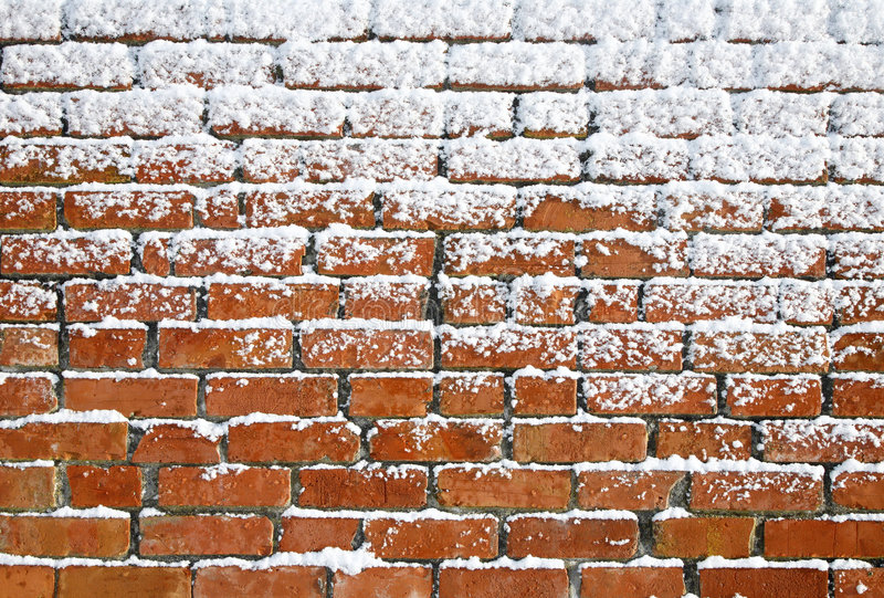 Neve che attacca ad un vecchio muro di mattoni. immagini stock