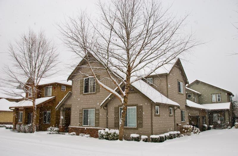 Neve che cade, coprendo le case e stree residenziali immagini stock libere da diritti