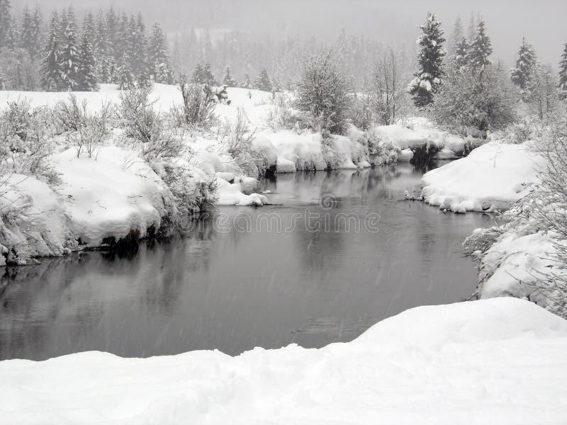 Neve che cade su un fiume con le banche nevose in Whistl immagine stock