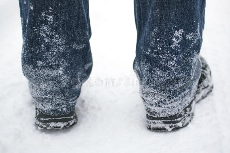 Neve congelata sui jeans e sugli stivali neri di un uomo nell'inverno, retrovisione fotografia stock