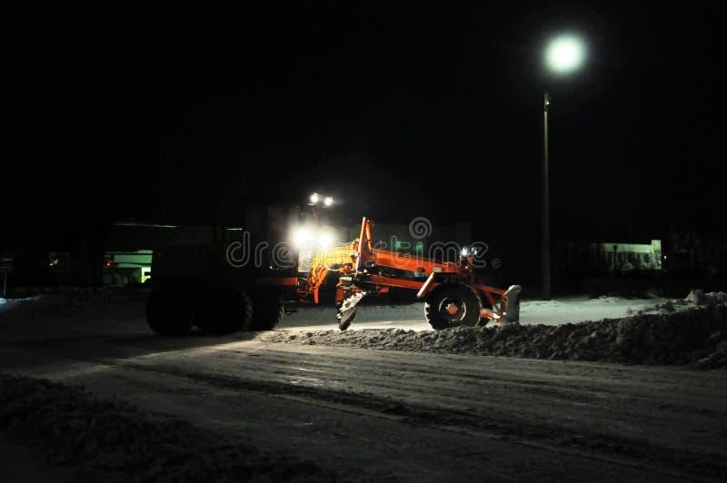 Neve da limpeza do trator da remoção de neve, silhueta do caminhão que trabalha na estrada da limpeza da noite, infraestrutura da imagens de stock royalty free