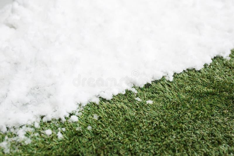 Neve da reunião no fim da grama verde acima - entre o inverno e o fundo do conceito da mola imagem de stock royalty free
