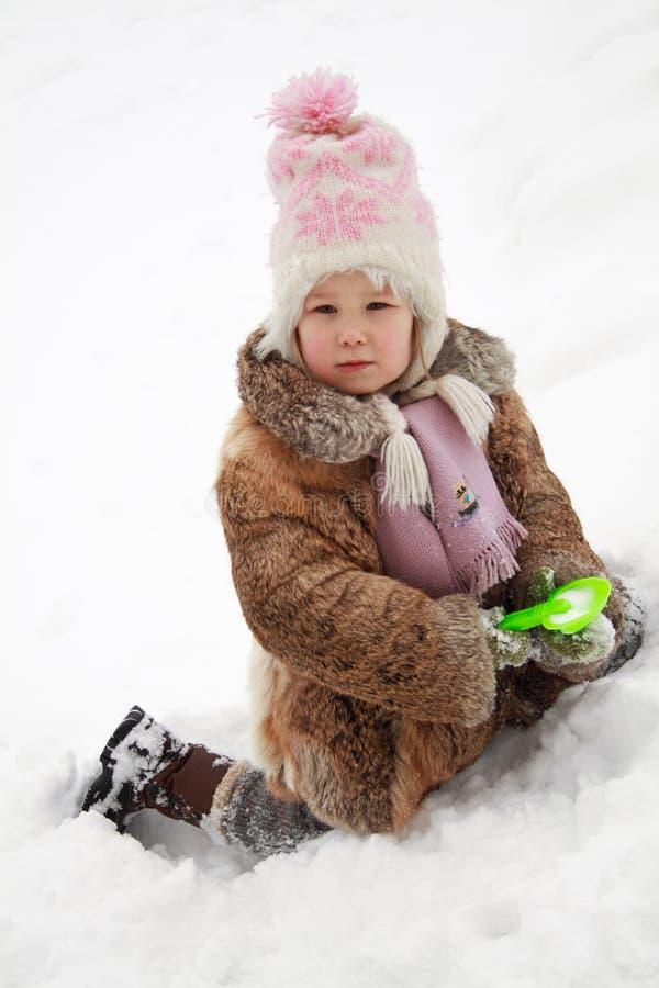 Neve de escavação da menina foto de stock