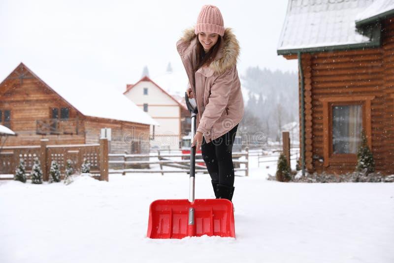 Neve de limpeza da jovem mulher com a pá perto da casa foto de stock royalty free