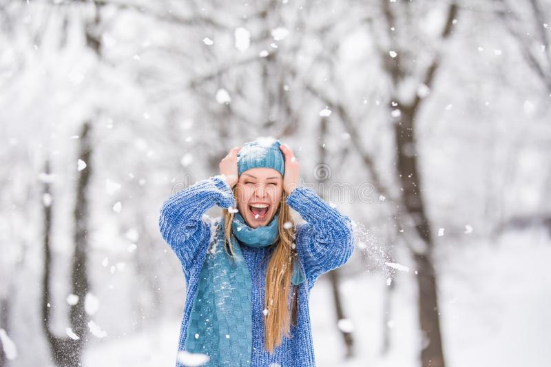 Neve de sopro da menina do inverno Beleza Girl modelo adolescente alegre que tem o divertimento no parque do inverno foto de stock