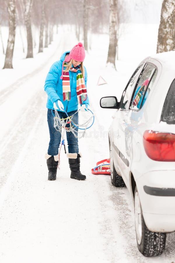 Neve della donna che si leva in piedi con le catene di gomma dell'automobile fotografia stock libera da diritti