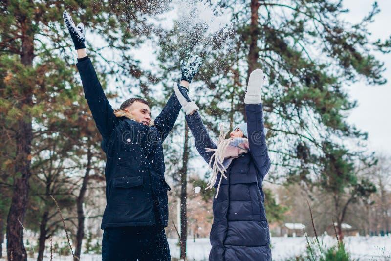 Neve di lancio delle belle coppie amorose su nella gente della foresta di inverno divertendosi all'aperto immagine stock libera da diritti