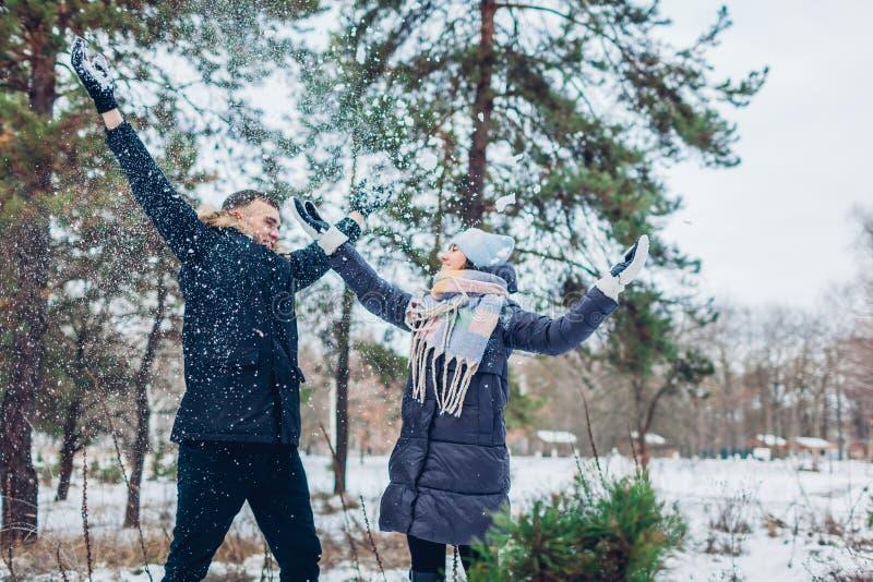 Neve di lancio delle belle coppie amorose su nella gente della foresta di inverno divertendosi all'aperto immagine stock