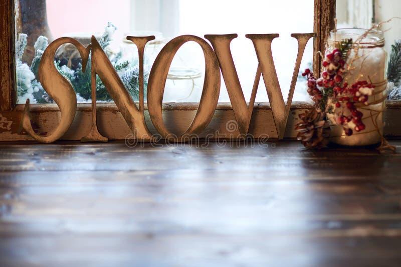 NEVE di parola - lettere di legno e supporto di candela decorato con la pigna e ashberry sul davanzale fotografia stock libera da diritti