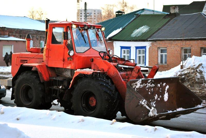 Neve di pulizia del trattore arancio luminoso dell'escavatore sulla strada lungo le case residenziali, inverno nevoso a Harkìv fotografia stock