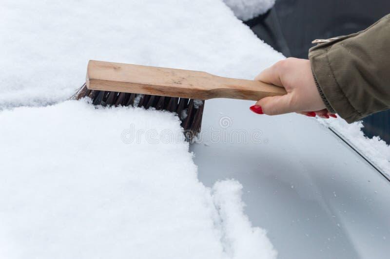 Neve di pulizia della donna dall'automobile con la spazzola fotografie stock