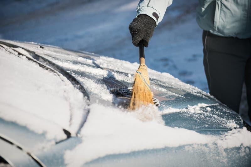 Neve di pulizia della donna dalla sua automobile con una scopa fotografia stock libera da diritti