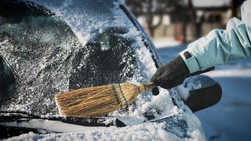 Neve di pulizia della donna dalla sua automobile con una scopa fotografie stock libere da diritti