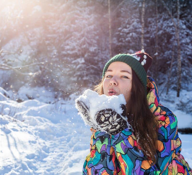 Neve di salto della ragazza di inverno di bellezza nel parco gelido di inverno all'aperto Fiocchi di neve di volo Giorno pieno di immagine stock