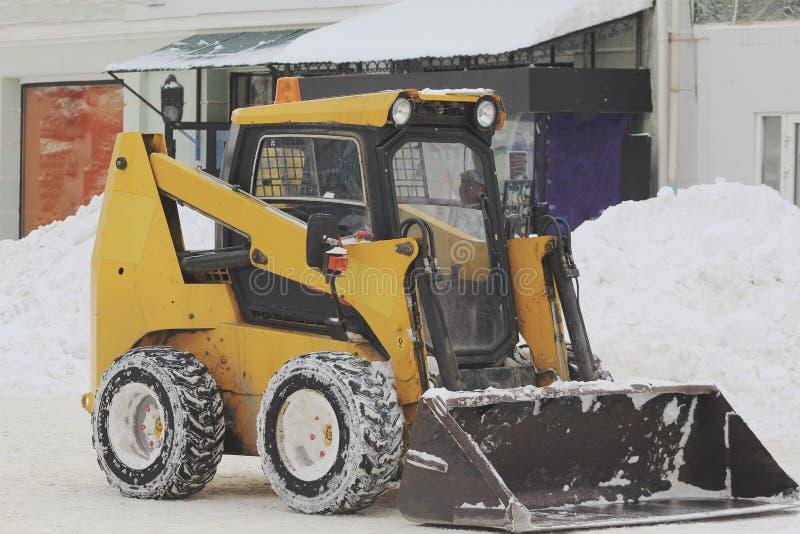Neve di schiarimento dalla strada con il bulldozer nella città nell'inverno fotografia stock libera da diritti