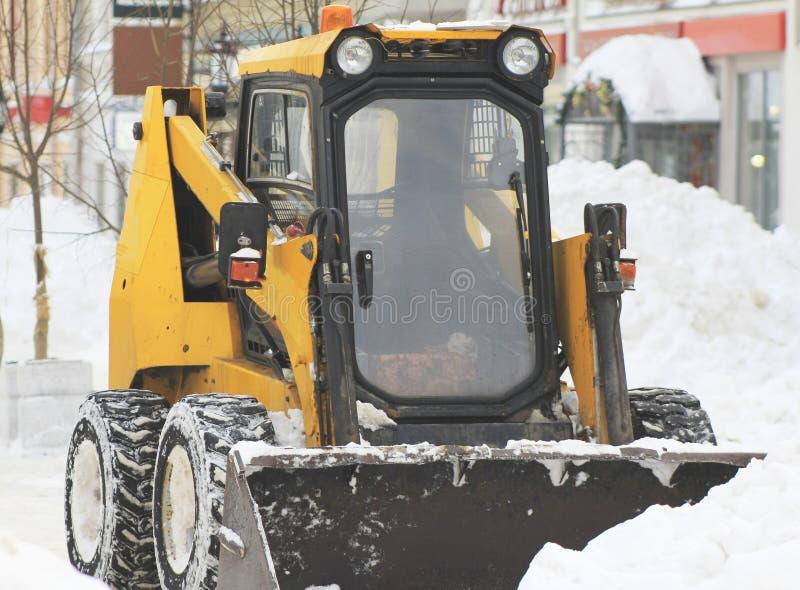 Neve do esclarecimento da estrada com a escavadora na cidade fotografia de stock