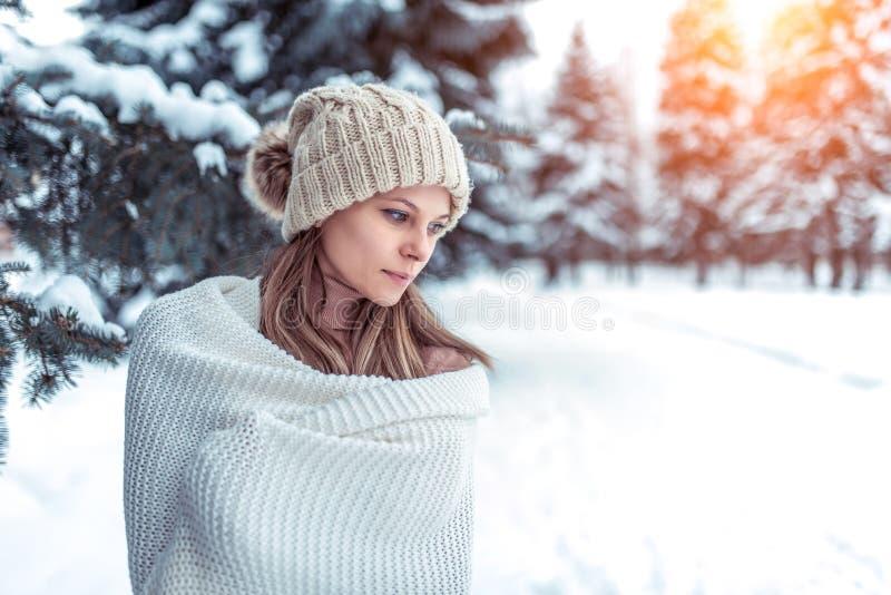 Neve do fundo da mulher do inverno do retrato do close up e árvores de Natal Chapéu morno branco do inverno, grande manta de lã l foto de stock royalty free