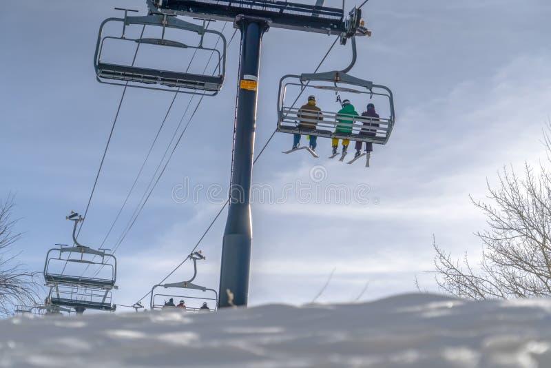 Neve e esquiadores em elevadores de esqui contra o céu brilhante imagens de stock royalty free