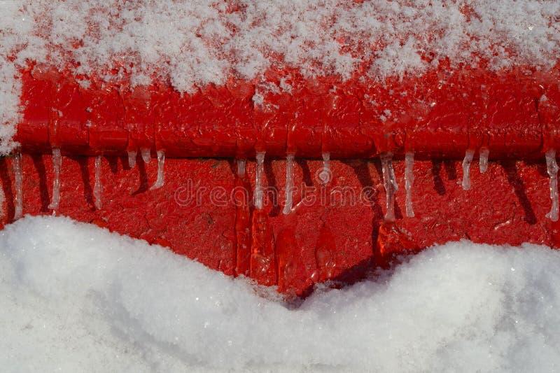 Neve e ghiaccioli astratti sul fondo rosso del ferro immagine stock