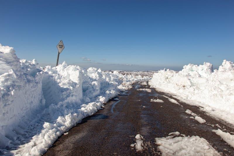 A neve empilhou altamente ao lado de uma estrada do charneca ap?s um blizzard foto de stock