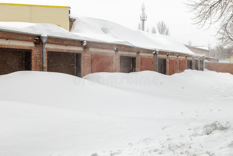 A neve enorme deposita perto das portas da garagem no inverno durante o blizzard fotografia de stock