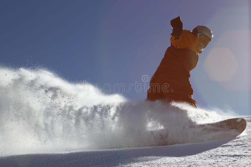 A neve espirra sob o snowboarder foto de stock