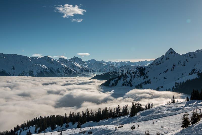 Neve na parte superior das montanhas e da névoa abaixo do vale fotografia de stock royalty free