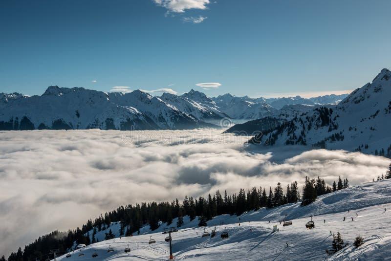 Neve na parte superior das montanhas e da névoa abaixo do vale foto de stock royalty free