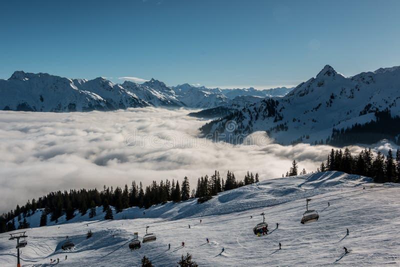 Neve na parte superior das montanhas e da névoa abaixo do vale foto de stock