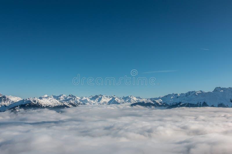 Neve na parte superior das montanhas e da névoa abaixo do vale fotografia de stock